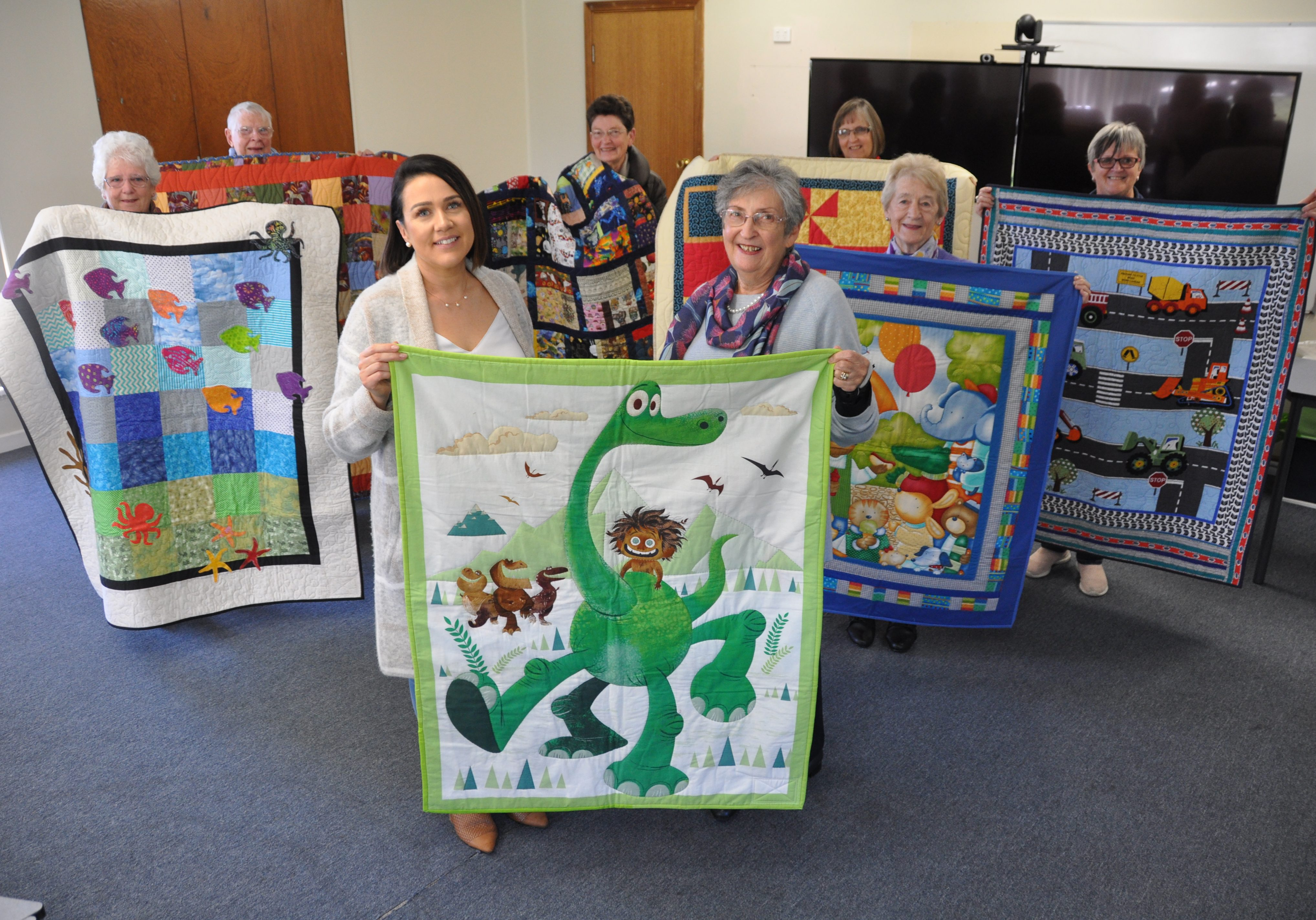 TREASURED SUPPORT: ac.care foster care placement support worker Emily Wastell with Kaye Dalgarno and members of the Pine Tree Quilters during the recent handover of 30 hand-made quilts to be donated to children in state care on the Limestone Coast.